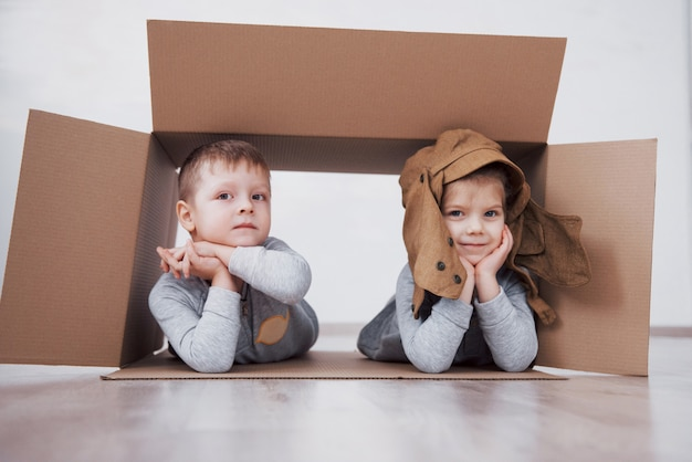 Два маленьких детей, мальчик и девочка, играя в картонные коробки. концепция фото. дети веселятся