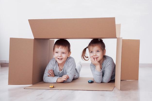 Двое маленьких детей, мальчик и девочка, играющие в маленькие машинки в картонных коробках. концептуальное фото. дети веселятся. концептуальное фото. дети веселятся