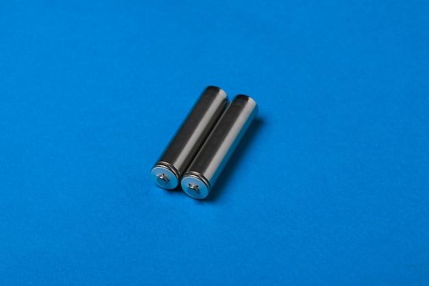 Две батарейки аа на синем фоне. аккумуляторный источник питания.