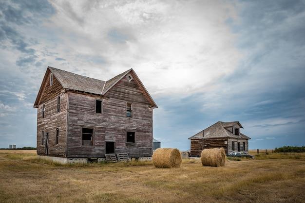 カナダのゴーストタウン、ロブサートサスカチュワンにある2つの廃屋の干し草の俵とクラシックカー