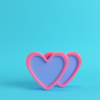 Two abstract pink hearts on bright blue background
