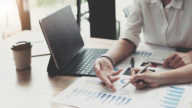 会社の予算と財務計画に関する計算をオフィスルームの机で共有する2人の会計士のディスカッション分析