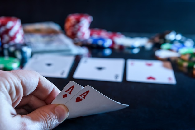 손에 두 개의 에이스와 블랙 도박 칩