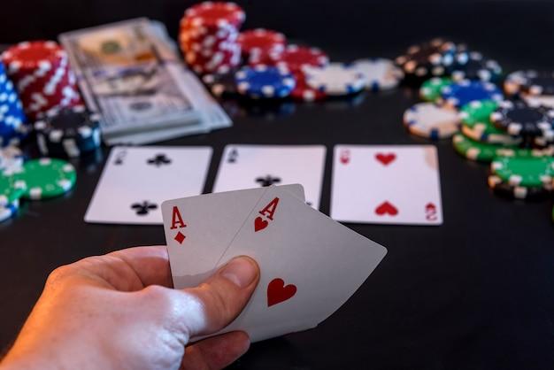 手に2つのエースと黒のギャンブルチップ