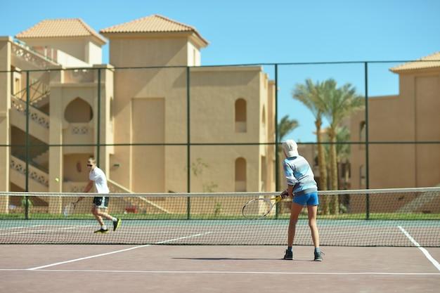 テニスコートで遊んでいる2人のアクティブな兄弟