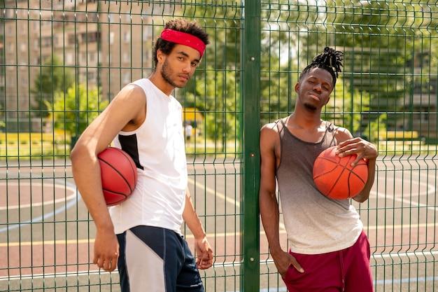 バスケットボールコートを囲むフェンスのそばに立っているスポーツウェアの2人のアクティブな男