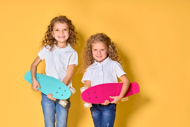 Two active and happy girls with curly hair having fun with penny board, smiling face stand skateboard