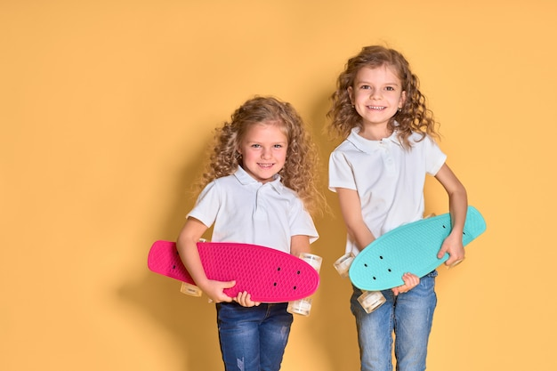 Two active and happy girls with curly hair having fun with penny board,