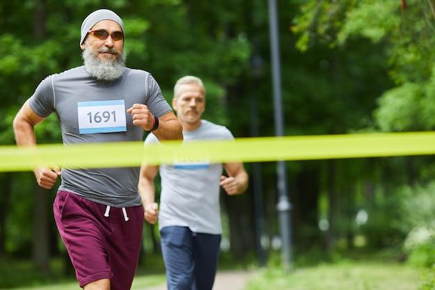 あごひげを生やした男が最初、ミディアムロングショットでマラソンレースを終えた2人のアクティブなスポーティな年配の男性