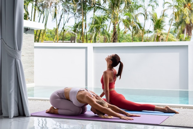 Two active woman asian and caucasian go outside practice yoga at luxury villa poolside