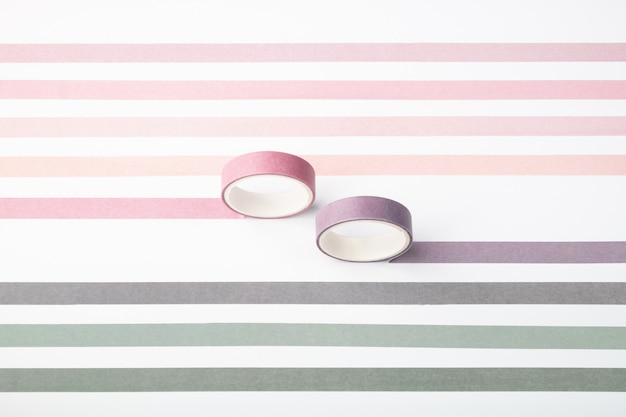 Two adhesive tape rolls and parallel strips on white