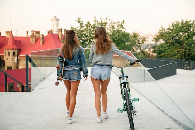Two adorable best girlfriends in stylish denim jackets and jeans shorts with bicycle and longboard while walking on the street in morning.