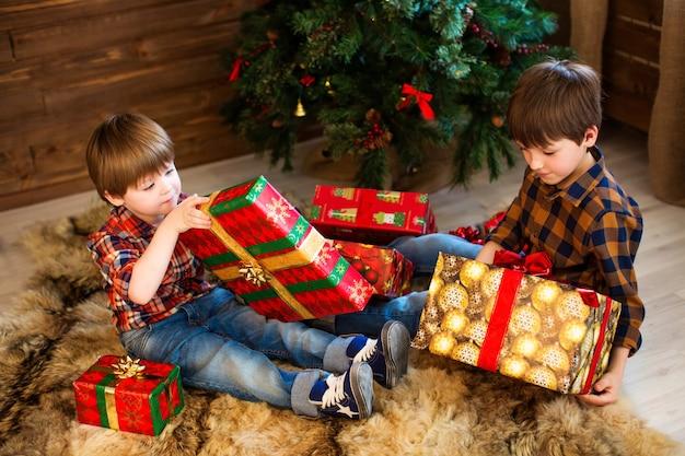 クリスマスにプレゼントを開く2人の愛らしい男の子