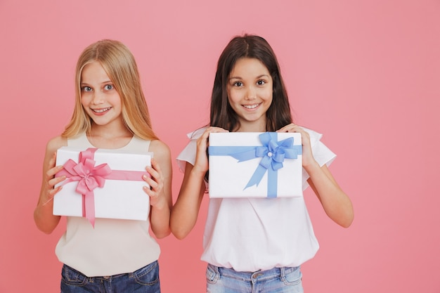 Two adorable caucasian girls 8-10 in casual clothing smiling at camera and holding present boxes with colorful bows, isolated over pink background