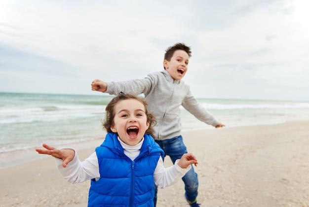 사랑스러운 두 아이, 소년과 소녀, 웃고 해변에서 놀고 있습니다.