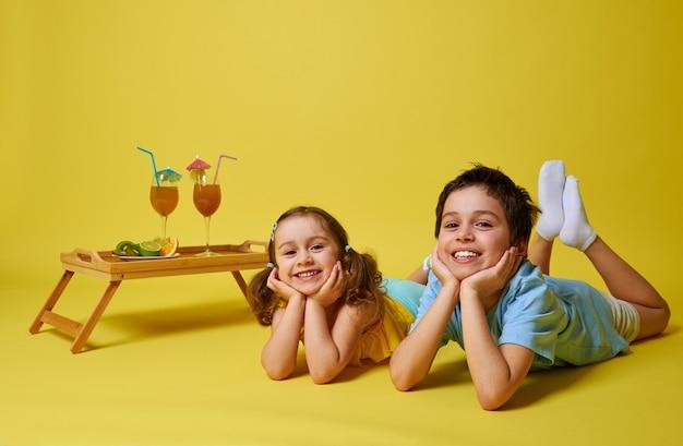 Двое очаровательных детей лежат на желтом фоне возле бамбукового подноса
