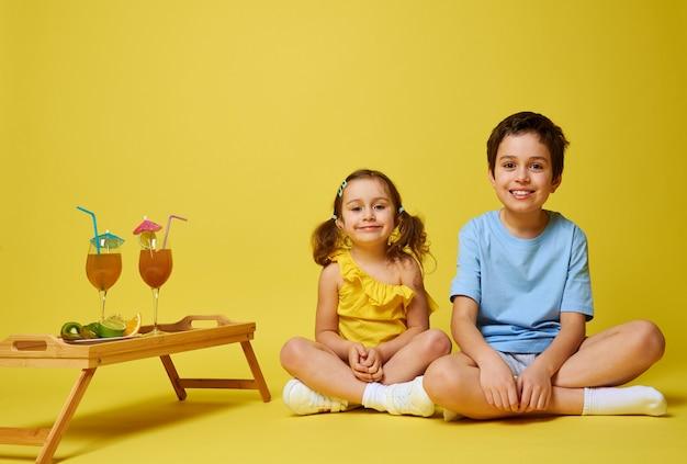 木製のサービングトレイの近くに蓮華座に座っている2人の愛らしい子供たち