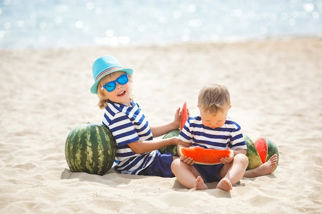 Two adorable children sitting at the sea shore and eating watermelon. two brothers having fun on the beach. pretty little boys outdoors