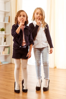 Two adorable girl dressed in stylish clothes and shoes.