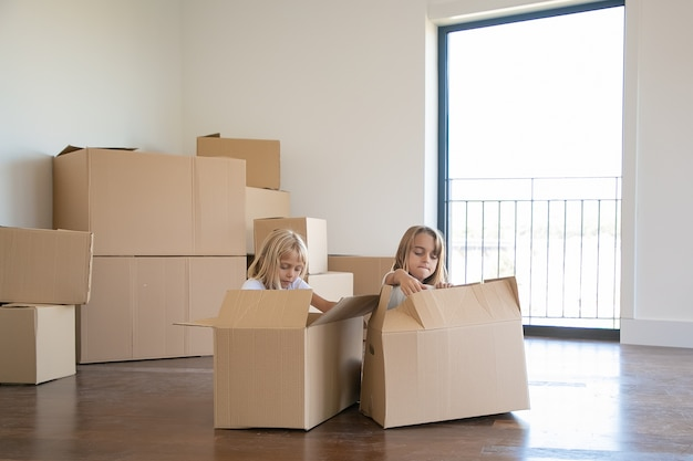 Two adorable girls unpacking things in new apartment, sitting on floor near open cartoon boxes