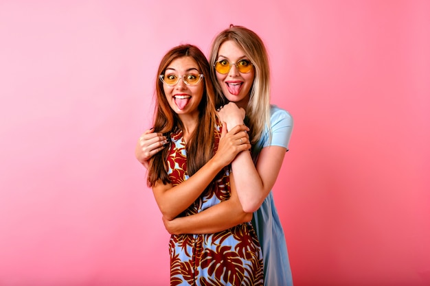 Two adorable happy young women having fun together showing tongues