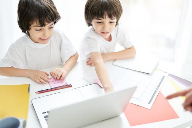 두 명의 사랑스러운 라틴 소년, 집중하고 있는 형제, 함께 테이블에 앉아 노트북 화면을 보고 있습니다. 집에서 온라인 수업을 하는 어린 아이들. 잠금 개념 중 원격 교육