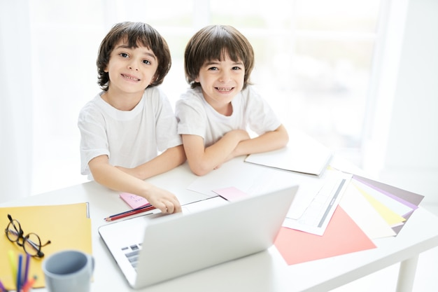 Two adorable latin boys, brothers smiling at camera while sitting together at the table and using laptop. little kids having online lesson at home. children, e learning concept