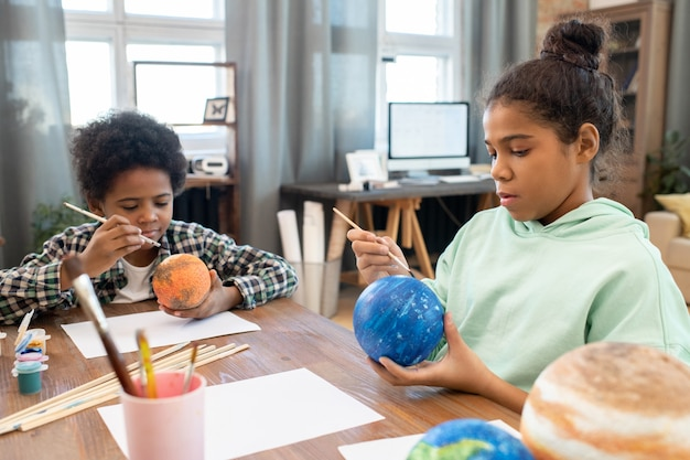 Two adorable mixed-race siblings in casualwear painting planets by table in home environment while preparing for lesson of astronomy