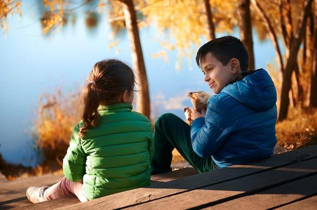 川の桟橋に座って、青と緑のジャケットを着て、おいしいクロワッサンを食べて、秋の川の背景で屋外の時間を楽しんでいる2人の愛らしいプレティーンの美しい子供たち