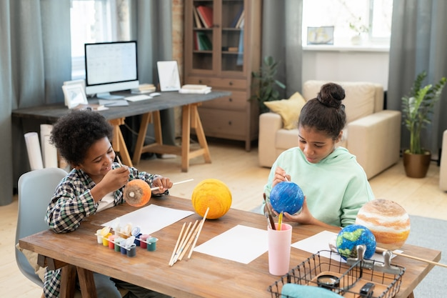 Two adorable siblings of elementary age painting planets while sitting by table in home environment and preparing for the lesson of astronomy