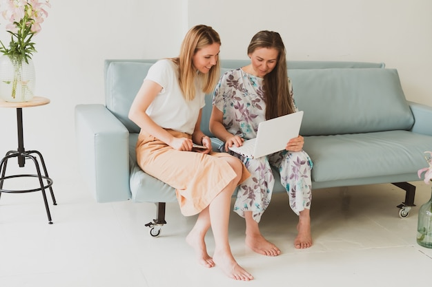 Two adorable young women chatting at home on the couch, drinking coffee and working on a laptop