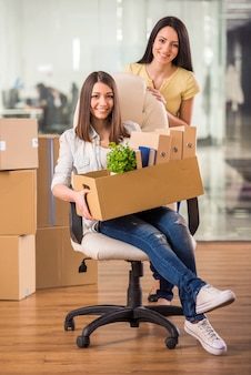 Two adult businesswomen moving into a new office.