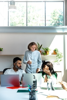 За офисным столом разговаривают двое взрослых коллег. другой коллега пьет кофе на заднем плане. скопируйте пространство. вертикальное изображение. концепция запуска.