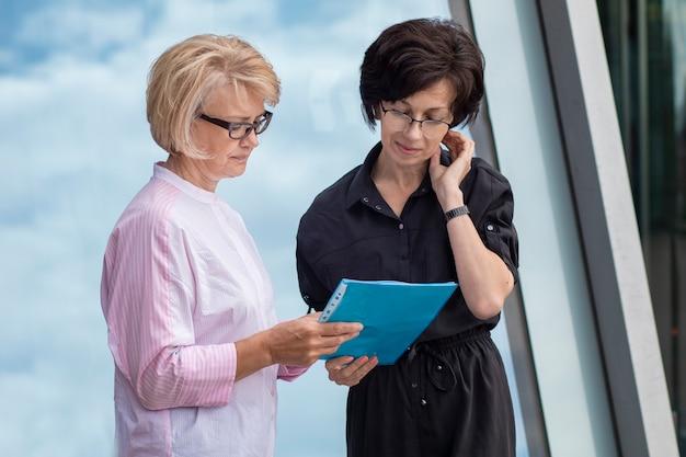 Две взрослые зрелые женщины-предприниматели в очках, работая с бумагами