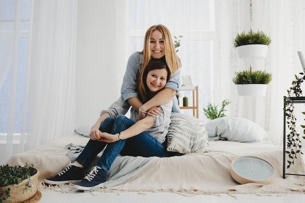 Две взрослые сестры обнимают друг друга, сидя на белой кровати