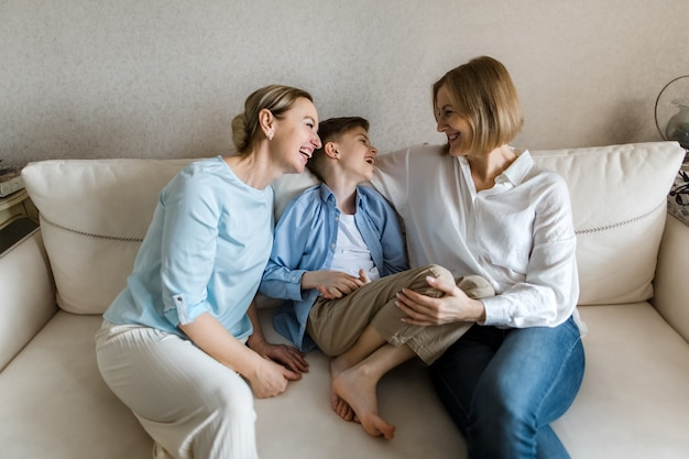Две взрослые женщины и ребенок сидят на диване, болтают и улыбаются