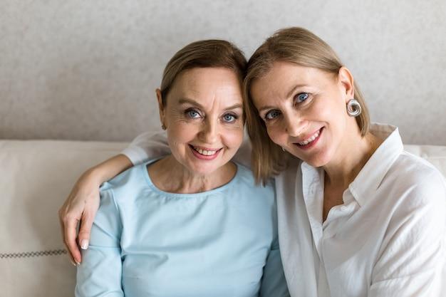 Две взрослые женщины сидят на диване, обнимая