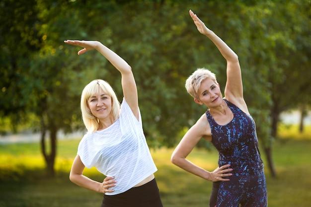 2人の大人の女性が夏の公園でスポーツに行きます