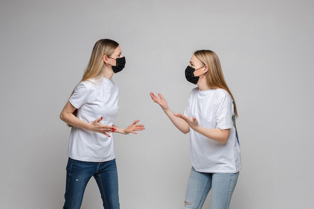 Two adult women in masks arguing.