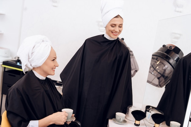 Two adult women with towels on their heads drinking coffee.