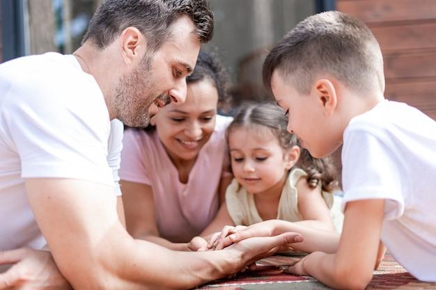 두 명의 성인과 두 명의 어린이가 팔미스트 놀이를 하고, 서로의 손과 손바닥을 살펴보고, 나란히 누워 여름 주말에 함께 즐거운 시간을 보내세요.