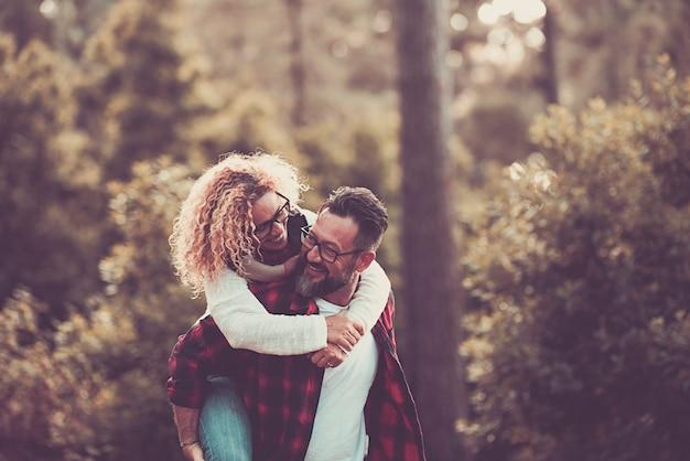 木を背景に木で楽しみ、一緒に笑う 2 人の大人