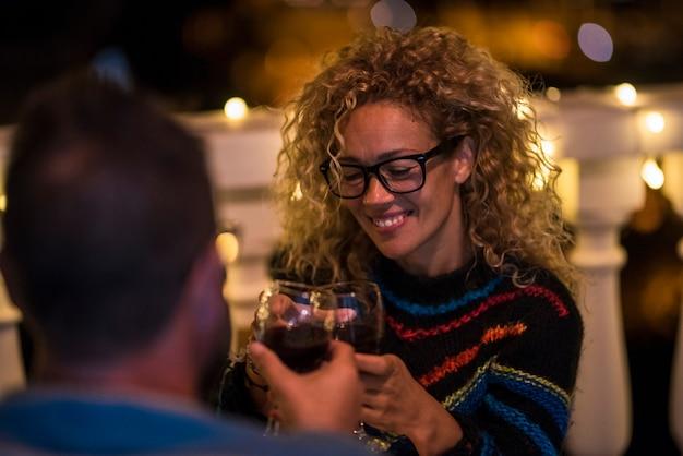 二人の大人の関係は夜に夕食に出かけ、一緒に食事をします-レストランでチリンと鳴る男と女-男と女の顔の後ろ