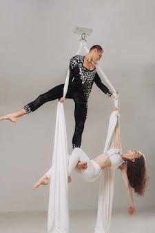 Two aerial gymnasts performing silk acrobatics