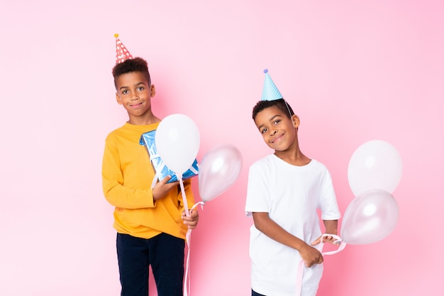 Two african american brothers holding balloons and a gift over isolated pink background