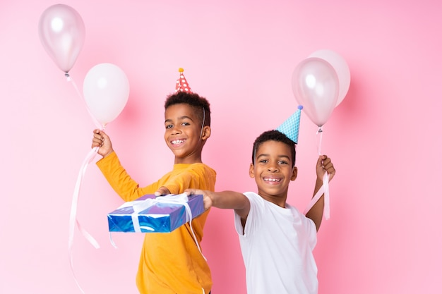 Two african american brothers holding balloons and a gift over isolated pink wall