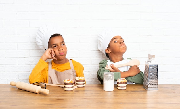 Two african american brothers kids dressed as chef and thinking
