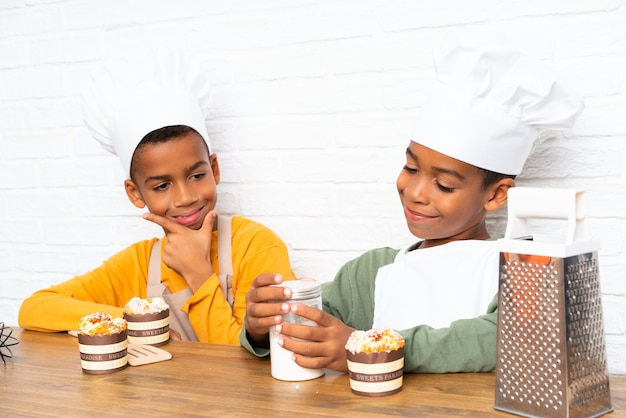Two african american brothers kids dressed as chef