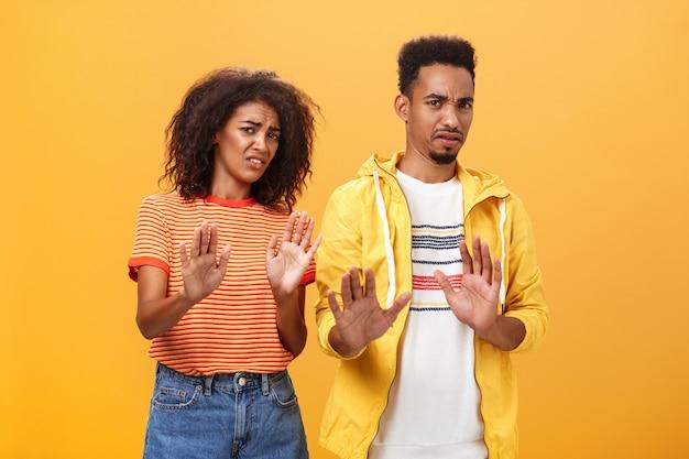 嫌悪感から顔をゆがめた拒否と拒否のジェスチャーで胸の近くに手を示している2人のアフリカ系アメリカ人の友人