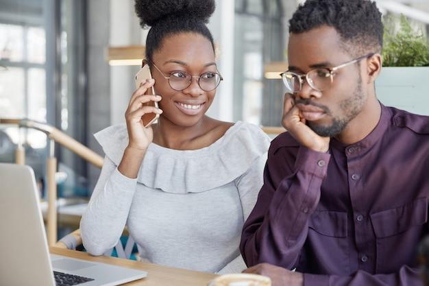 Два афроамериканских сокурсника встречаются вместе, чтобы работать над проектом или готовиться к урокам: счастливая темнокожая женщина разговаривает с другом по мобильному телефону.